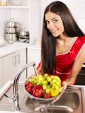 Woman washing fruit at kitchen. Stock Photo