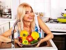 Woman washing fruit at kitchen. Royalty Free Stock Photos