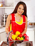 Woman washing fruit at kitchen. Stock Images