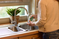 Woman washing a glass at the kitchen sink. Under running water from the tap, close up with her back to the camera Stock Photos