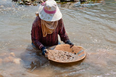 Woman washing gold in river Stock Image