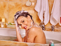 Woman washing hair in bubble bath Royalty Free Stock Photography