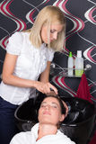 Woman washing hair in salon sink Stock Image