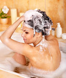 Woman washing hair by shampoo . Stock Photography