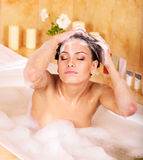 Woman washing hair by shampoo . Royalty Free Stock Image