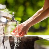Woman washing hands in a city fountain Royalty Free Stock Photography