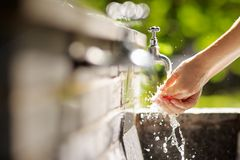 Woman washing hands in a city fountain Stock Photos