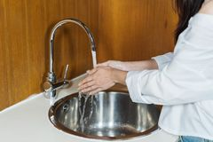 Woman washing hands in kitchen stock photo
