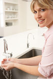 Woman Washing Hands At Kitchen Sink Stock Images