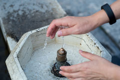 Woman washing hands on public fountain Stock Photo