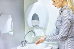 Woman washing hands in restroom Royalty Free Stock Photography
