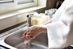 Woman washing hands in a sink with tap water. At home stock photography