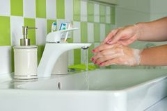 Woman washing hands with soap in the bathroom. Royalty Free Stock Images