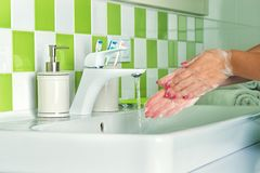 Woman washing hands with soap in the bathroom. Woman washing hands stock image