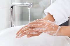 Woman washing hands with soap over sink in bathroom. Closeup royalty free stock image