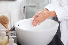 Woman washing hands with soap over sink in bathroom. Closeup royalty free stock photography
