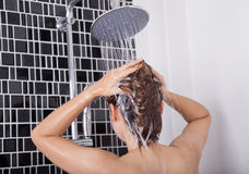 Woman washing head and hair in the rain shower by shampoo, rear Royalty Free Stock Photos