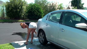 Woman washing her car stock video