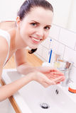 Woman washing her face in bathroom Royalty Free Stock Images