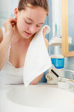 Woman washing her face with clean water in bathroom Royalty Free Stock Images