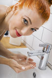 Woman Washing her Face While Looking at the Camera Royalty Free Stock Images