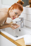 Woman Washing her Face While Looking at the Camera Stock Image
