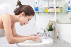 Woman washing her face with water above bathroom sink. Royalty Free Stock Photos