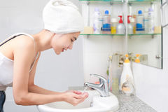 Woman washing her face with water above bathroom sink. royalty free stock images
