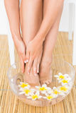 Woman washing her feet in a bowl of flower Stock Photography