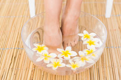 Woman washing her feet in a bowl of flower Stock Photos