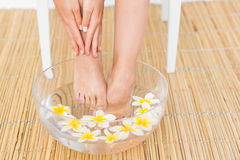 woman washing her feet in a bowl of flower Royalty Free Stock Image