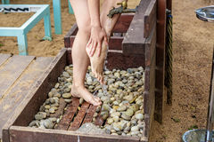 Woman washing her feet on the sand beach. Place for washing the feet is made of wooden planks. The flooring is strewn with pebbles. Summer vacation at the Stock Image