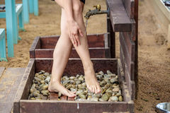 Woman washing her feet on the sand beach. Royalty Free Stock Images