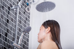 Woman is washing her hair and face by rain shower Royalty Free Stock Images