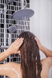 Woman is washing her hair and face by rain shower, rear view Stock Photo