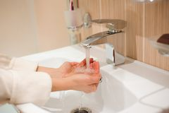 A woman washing her hands in the sink stock images
