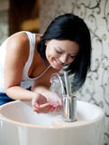 Woman washing her hands in the sink Stock Images