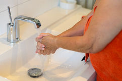 Woman washing her hands at the sink Royalty Free Stock Images