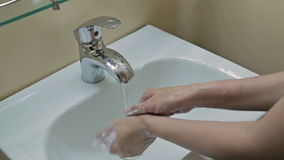 Woman washing her hands with soap in bathroom stock video