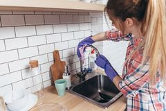 Woman washing the kitchen sink and faucet.  stock photography
