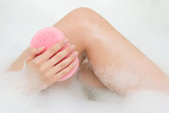 Woman washing legs in bath with sponge Royalty Free Stock Images