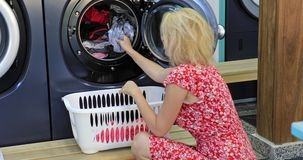 Woman washing machine. A blonde caucasian maid woman unloads washing machine with clothing to laundry basket. Smiling housewife dressed in 50s style doing stock footage