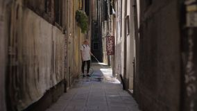 Woman washing paved alleyway in Burano, Italy. Venice, Italy - April 21, 2018: Woman using a hose to wash paved path in alley between old houses stock video footage