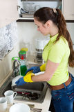 Woman washing plates in home Stock Images