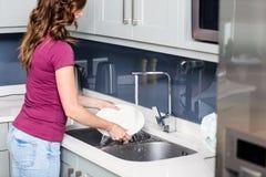 Woman washing plates at kitchen sink Stock Image