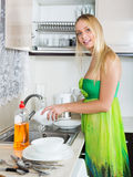 Woman washing plates with sponge Royalty Free Stock Photo