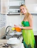 Woman washing plates with sponge Stock Photo