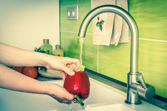 Woman washing red pepper for salad - retro style Royalty Free Stock Photos