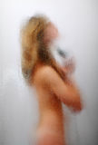 Woman washing in shower cabin. Blurred silhouette of nude girl having a shower, side view. In the foreground glass surface patterned. Focus on the forefront Stock Photography