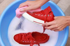Woman washing sneakers with rag over plastic basin,. Closeup Royalty Free Stock Image